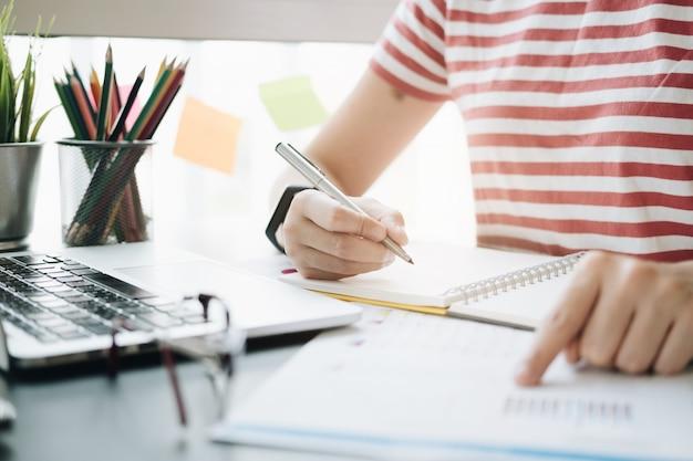 Feche acima das mãos da mulher que apontam o relatório financeiro e que escrevem no bloco de notas.