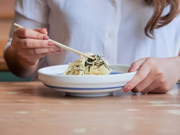 Feche acima das mãos da mulher usando hashis para comer o macarronete no restaurante, conceito do tempo de almoço.