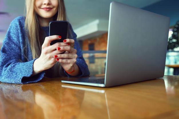 Feche acima das mãos das mulheres segurando o telefone celular