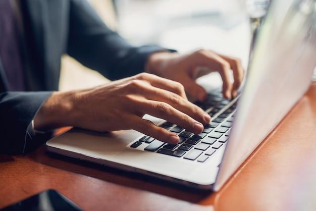 Feche acima das mãos de um homem de negócios em um teclado.