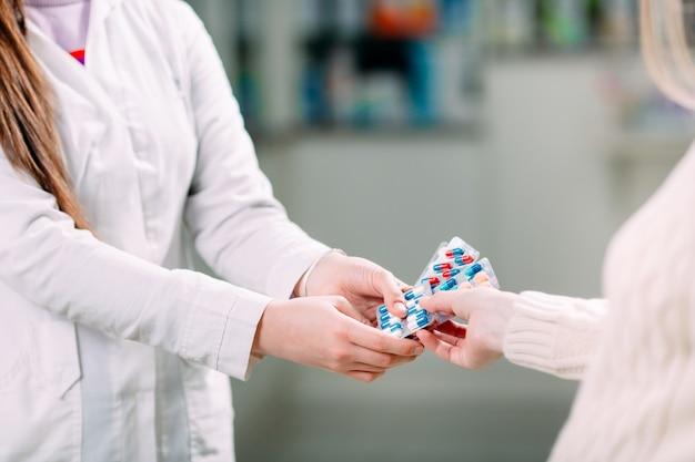 Feche acima das mãos de uma menina que compram comprimidos em uma farmácia.