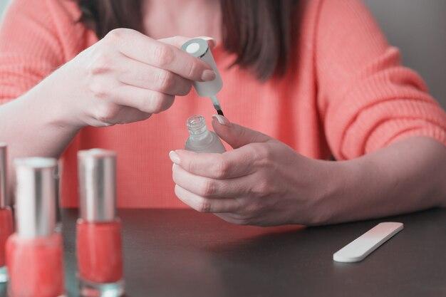 Feche acima das mãos de uma mulher nova que faça um manicure para casa.