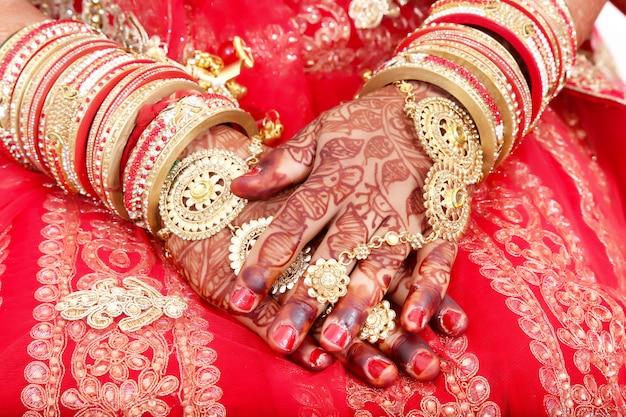 Feche acima das mãos decorativas da noiva indiana com joia dourada.