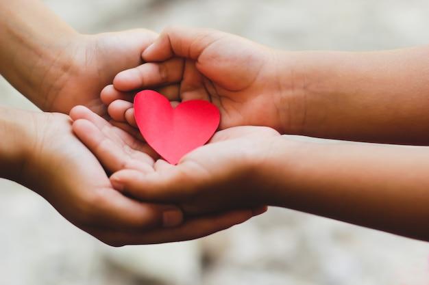 Feche acima das mãos do adulto e da criança que guardam o coração vermelho.