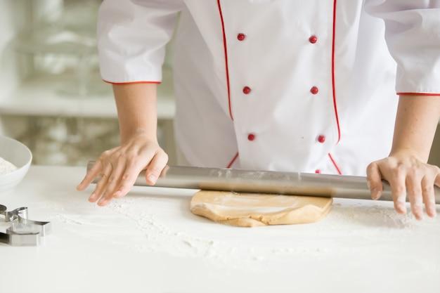 Feche acima das mãos do confeiteiro que rolam a massa do pão de ave