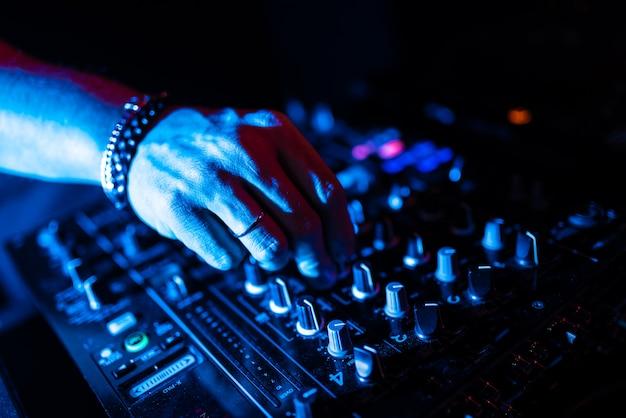 Feche acima das mãos do dj que controlam uma tabela da música em um clube noturno.