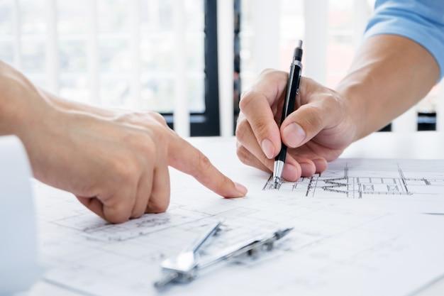 Feche acima das mãos do engenheiro discutindo um projeto de construção de edifícios no local de trabalho