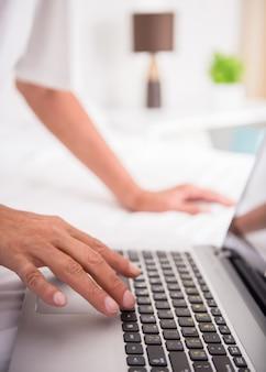 Feche acima das mãos do homem está usando o portátil.