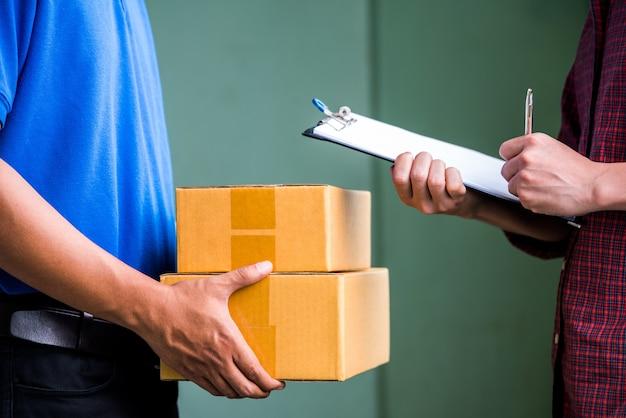 Feche acima das mãos do homem que assinam para obter seu pacote do entregador.