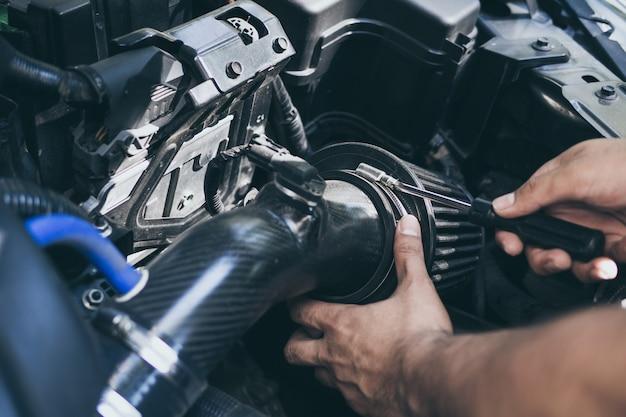 Feche acima das mãos do mecânico irreconhecível que fazem o serviço e a manutenção do carro. mudança de fluxo de ar