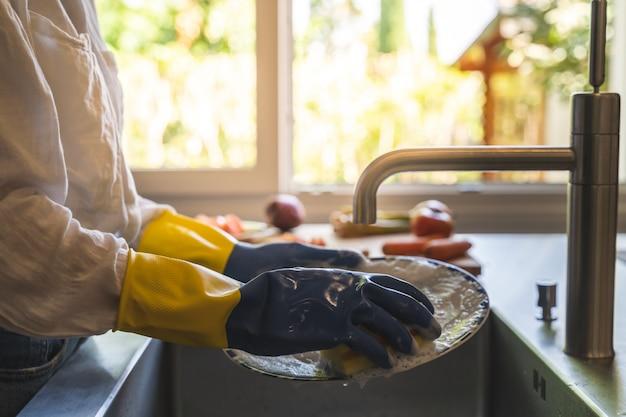 Feche acima das mãos fêmeas que lavam pratos.
