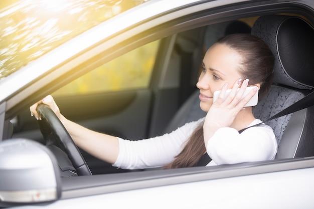 Feche acima das mãos femininas no volante