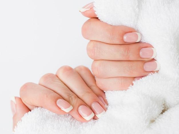 Feche acima das mãos manicured que guardam a toalha macia