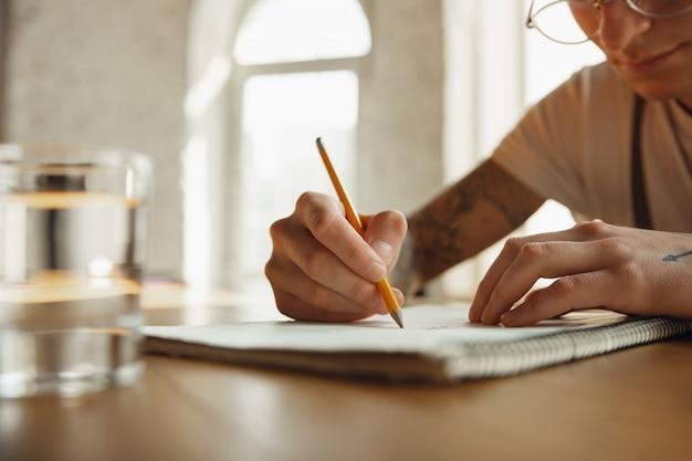 Feche acima das mãos masculinas, escrevendo em um conceito vazio de papel, educação e negócios