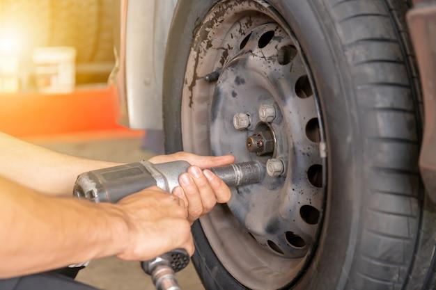 Feche acima das mãos mecânicas do reparo durante o trabalho de manutenção à arma pneumática para afrouxar uma porca da roda que muda o pneu do carro