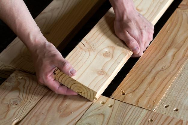 Feche acima das mãos musculares fortes do carpinteiro profissional que instalam pranchas novas de madeira naturais no conceito da reconstrução, da melhoria, da renovação e da carpintaria do assoalho do quadro de madeira.