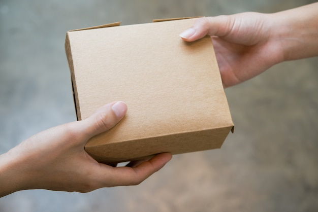 Feche acima das mãos que passam e que recebem o pacote marrom pequeno da caixa.