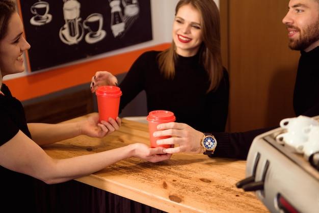Feche acima das mãos que tomam o copo do café quente do barista na loja dos confeitos.