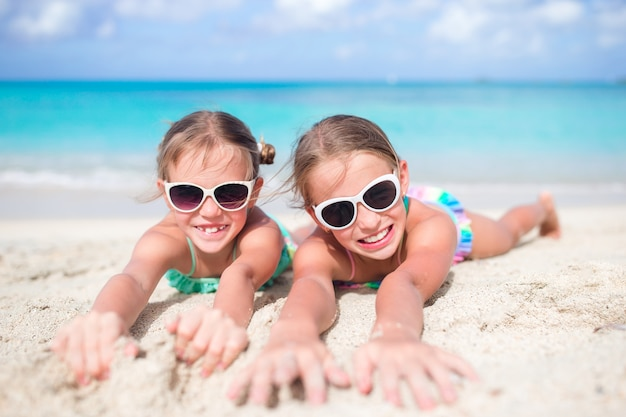Feche acima das meninas na praia arenosa. feliz, crianças, mentindo, ligado, morno, branca, praia arenosa