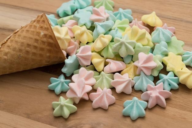 Feche acima das merengues da cor dos doces no cone de gelado.