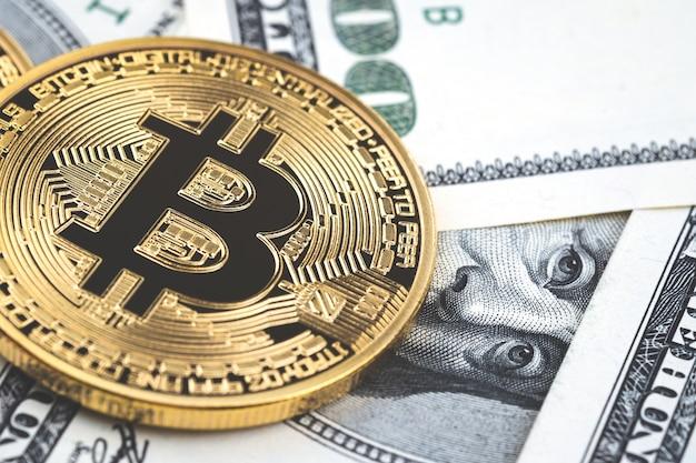 Feche acima das moedas do bitcoin do ouro em cem fundos das notas de dólar dos eu