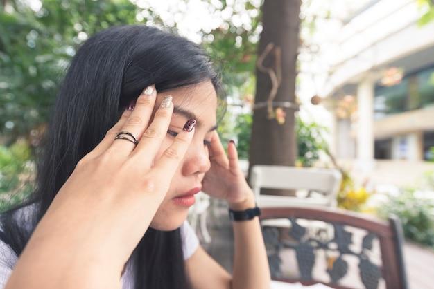 Feche acima das mulheres asiáticas é forçado na síndrome de park.office e no conceito do esforço de trabalho.