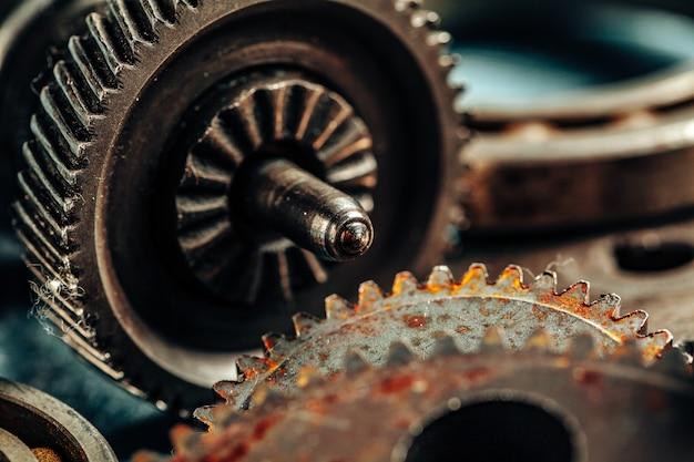 Feche acima das peças velhas do carro oxidado no fundo escuro