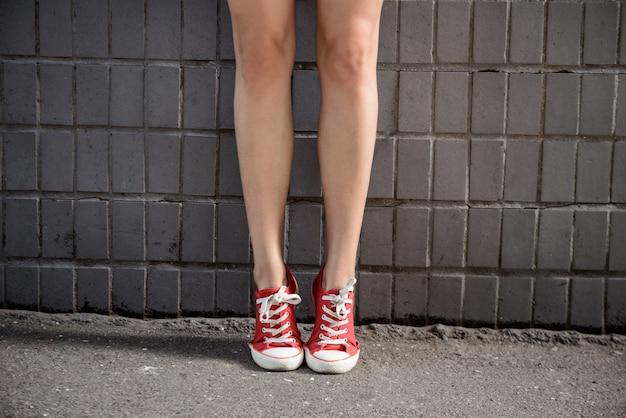 Feche acima das pernas da menina em keds sobre parede cinza.