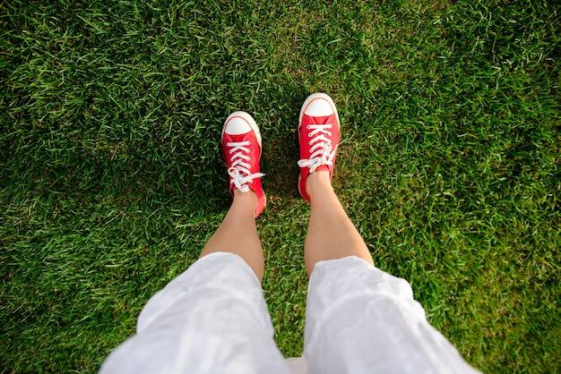 Feche acima das pernas da menina em keds vermelhos na grama.