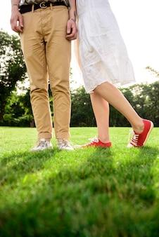 Feche acima das pernas do casal em keds na grama.