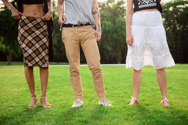 Feche acima das pernas dos amigos em keds na grama.