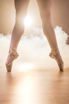 Feche acima das pernas espalhadas em sapatilhas de ponta