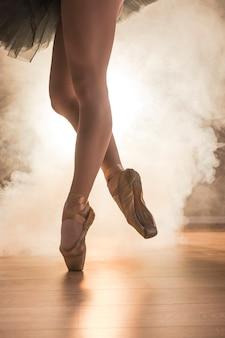 Feche acima das sapatas de bailado com fumo