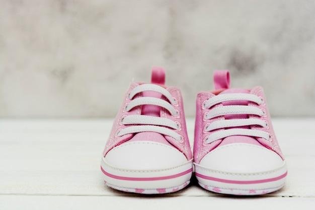 Feche acima das sapatilhas cor-de-rosa do bebê, sapatas do esporte fechem acima newbord, maternidade, conceito da gravidez com espaço da cópia.