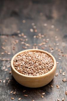 Feche acima das sementes de linho no fundo de madeira escuro. conceito de comida saudável para prevenir doenças cardíacas e excesso de peso.