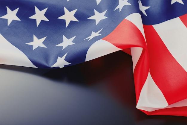 Feche acima de acenar a bandeira americana do eua nacional em uma obscuridade com espaço da cópia. dia da independência 4 de julho conceito