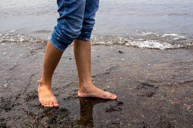 Feche acima de descalço vai para uma caminhada na água na praia com espaço da cópia.