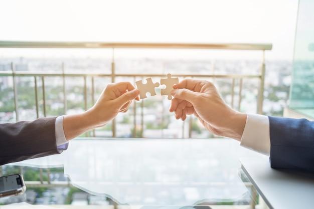 Feche acima de duas mãos conectam dois quebra-cabeça. conceito de negócio, sucesso e estratégia.