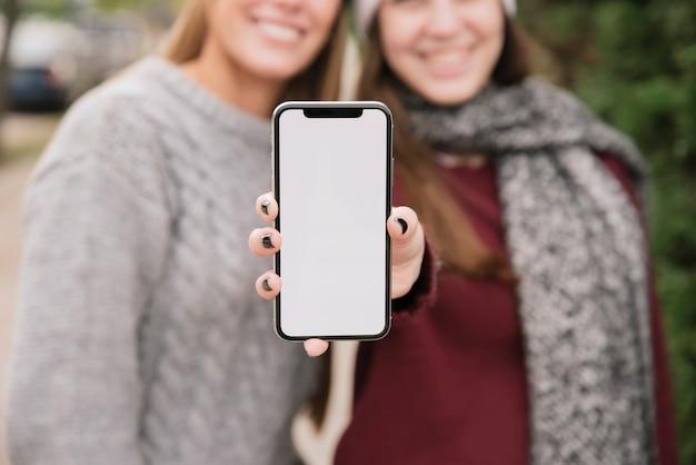 Feche acima de duas mulheres de sorriso que prendem o telefone nas mãos