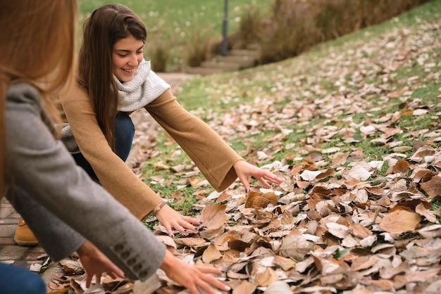 Feche acima de duas mulheres que jogam com as folhas no parque