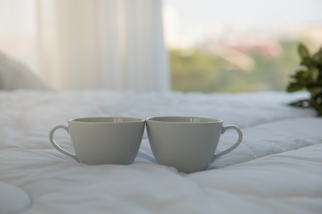 Feche acima de duas xícaras de café quentes brancas na cama no quarto com espaço da cópia da manhã.