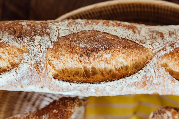 Feche acima de e aqueça o baguette cozido na cesta na tabela de madeira. feito pelo artesão.