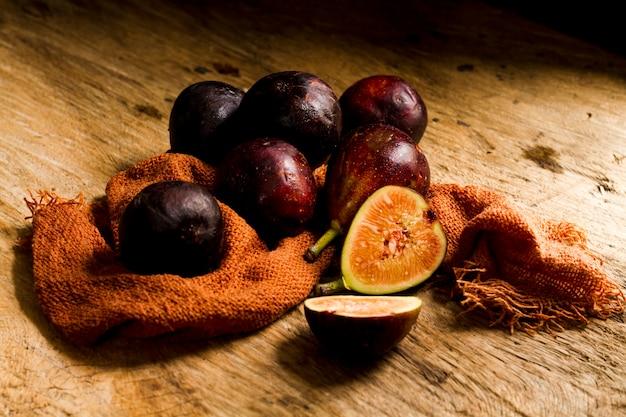 Feche acima de figos frescos cortados na mesa de madeira