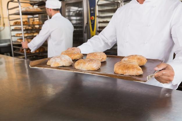 Feche acima de padeiro segurando bandeja de pão