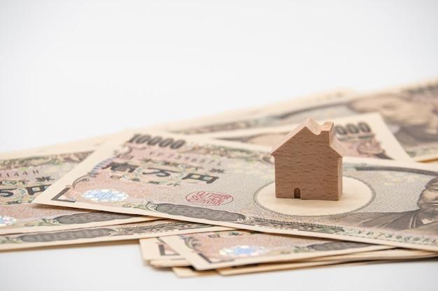 Feche acima de pouca casa de madeira na cédula japonesa do dinheiro dos ienes da moeda. economia do setor imobiliário do japão.