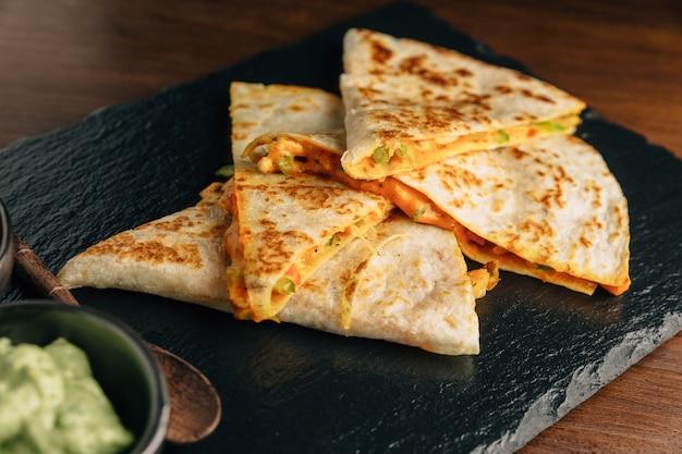 Feche acima de quesadillas cozidos da galinha e do queijo servidos com salsa e guacamole na placa de pedra.