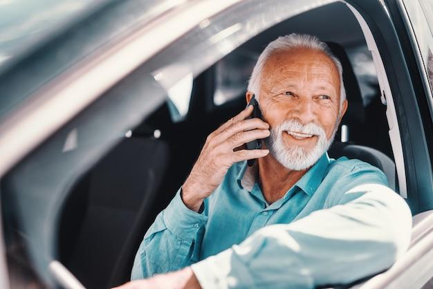 Feche acima de sorrir barbudo sênior falando ao telefone com o braço na janela aberta enquanto está sentado no carro.