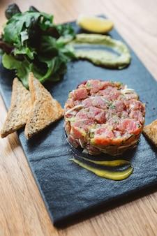 Feche acima de tartare picante do atum de bluefin com molho ácido e picante.