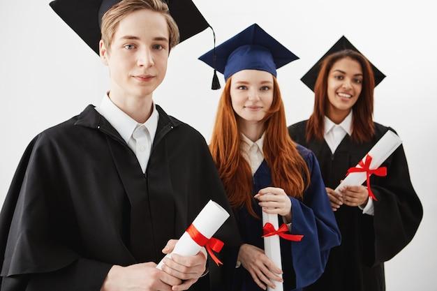 Feche acima de três graduados de faculdade internacionais felizes da raça misturada que sorriem exultando guardando diplomas. futuros advogados ou cirurgiões.