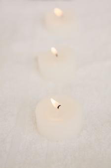 Feche acima de três velas iluminadas